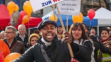 """Teilnehmer der DW Demo mit Plakat, auf dem zu lesen steht: """"Radio, das Tor zur Welt"""""""