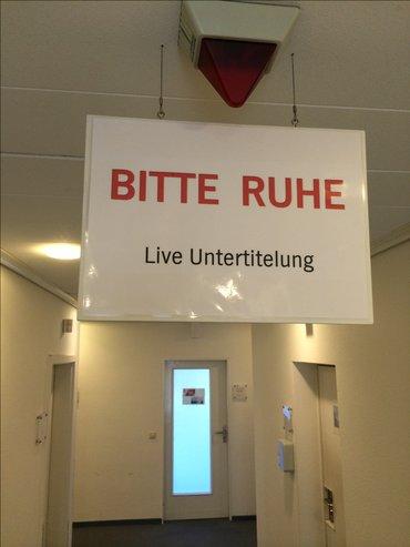 Auf einem Schild wir in einem Sender um Ruhe gebeten, da gerade eine Live-Untertitelung stattfindet