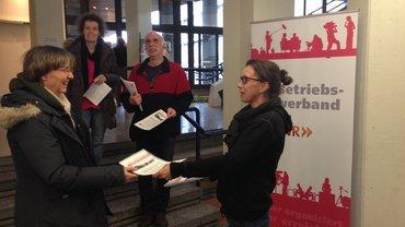 Kollegin von ver.di im SWR verteilt Flublätter, um die Mitarbeiter des Senders über die anstehende Tarifrunde zu informieren