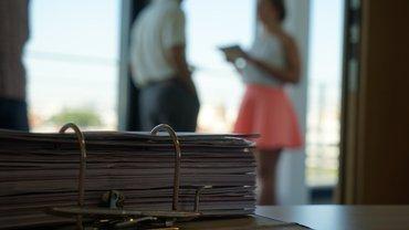 Aktenordner mit Unterlagen, im Hintegrund ein informelles Gespräch