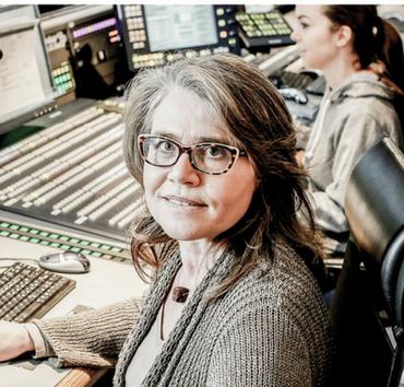 Eine Frau sitzt vor einem Studiopult und schaut in die Kamera