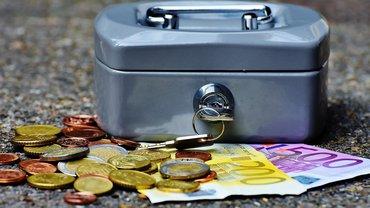 Münzen und Noten liegen vor einer geschlossenen Geldkassette, in der ein Schlüssel steckt