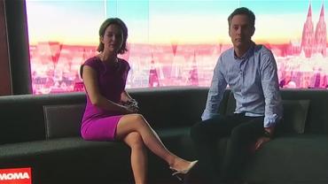 MoMa-Moderator*innen Anna Planken und Sven Lorig sitzen im dunklen Aufnahmestudio auf der roten Couch