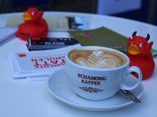 Kaffeetasse mit Milchkaffee und zwei roten ver.di-Kampfenten