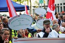 """Streikversammlung im NDR: Eine Frau hält eine Sprechblase mit der Aufschrift """"Marmor, Stein + Eisen bricht, aber die Gewerkschaft nicht"""" hoch"""