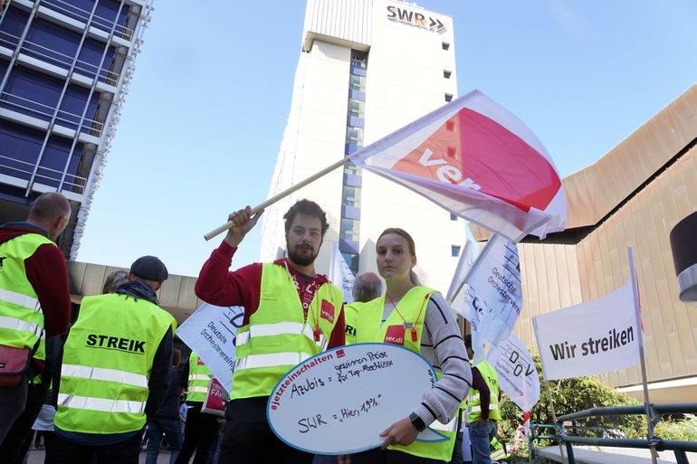 eine junge Frau und ein junger Mann in gelben ver.di-Streikwesten halten eine Sprechblase und eine ver.di-Fahne in der Hand. Dahinter sind weitre Streikende sowie das Sendegebäude des SWR zu sehen