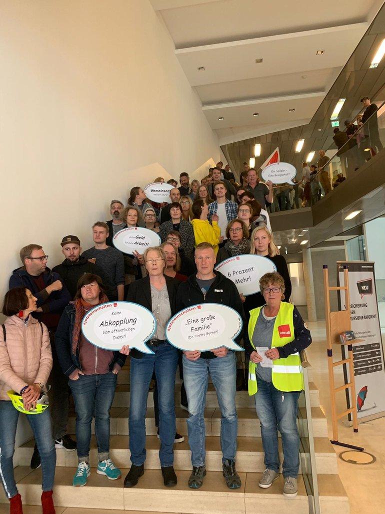 Beschäftigte von Radio Bremen haben sich für ein Gruppenbild auf der Treppe versammelt
