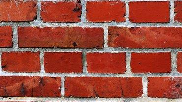 Eine rote Ziegelmauer mit grauen Fugen