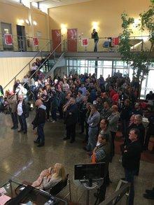 Eine große Gruppe von Menschen steht vor einer Treppe, einige sitzen auf den Treppenstufen