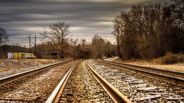 zwei Paar Schienen nebeneinander. Im Hintergrund eine einsame Herbst- oder Winterlandschaft.