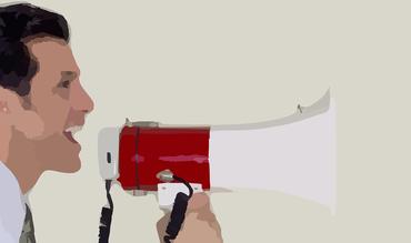 Ein Mann ruft in ein Megaphon.