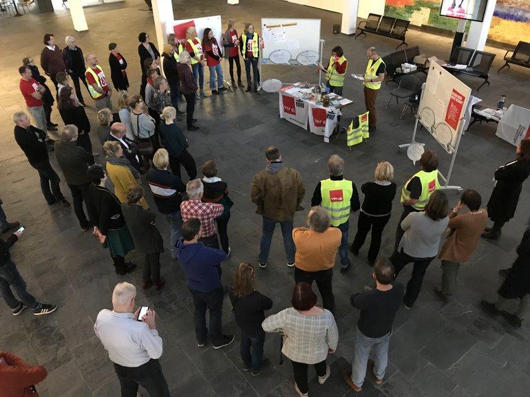 Beschäftigte im Foyer des rbb-Fernsehzentrums in Berlin, teilweise mit ver.di-Streikwesten bekleidet