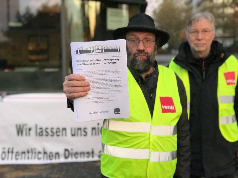 Ein Mann in ver.di-Streikweste mit einem Hut hält das aktuelle Flugblatt von ver.di NDR in die Kamera