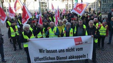 """Streikende NDR-Beschäftigte mit ver.di-Streikwesten hinter einem Banner, auf dem steht: Keine Abkoppelung vom ÖD"""""""
