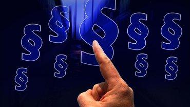 Paragraphen blau auf schwarzem Hintergrund, in der Mitte eine Hand, der Finger zeigt auf die Paragraphen