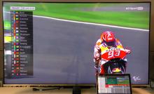 Motorrad-Rennfahrer auf einem Fernsehbildschirm. Unten rechts lehnt ein Tablet-PC am Fernseher