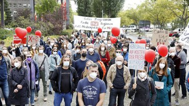 Viele freie Mitarbeiter*innen des rbb stehen mit Plakaten und Mundschutz auf einem Platz vor dem Sender und schauen in die Kamera, die auf der Bühne der Kundgebung steht